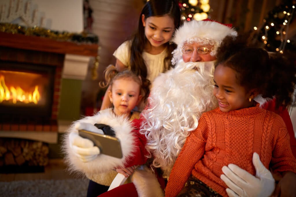 Santa Claus making selfie with three cute girls
