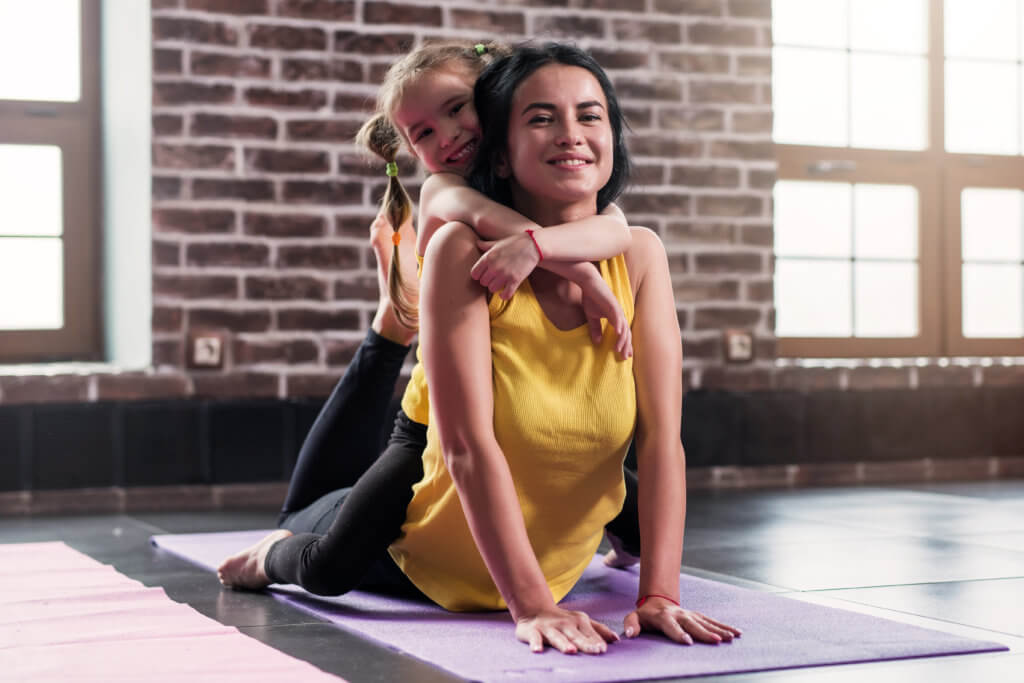 Young happy mother doing stretching exercise on mat while her smiling daughter hugging her in sports club.