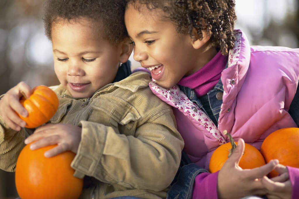 African sister and brother holding pumpkins