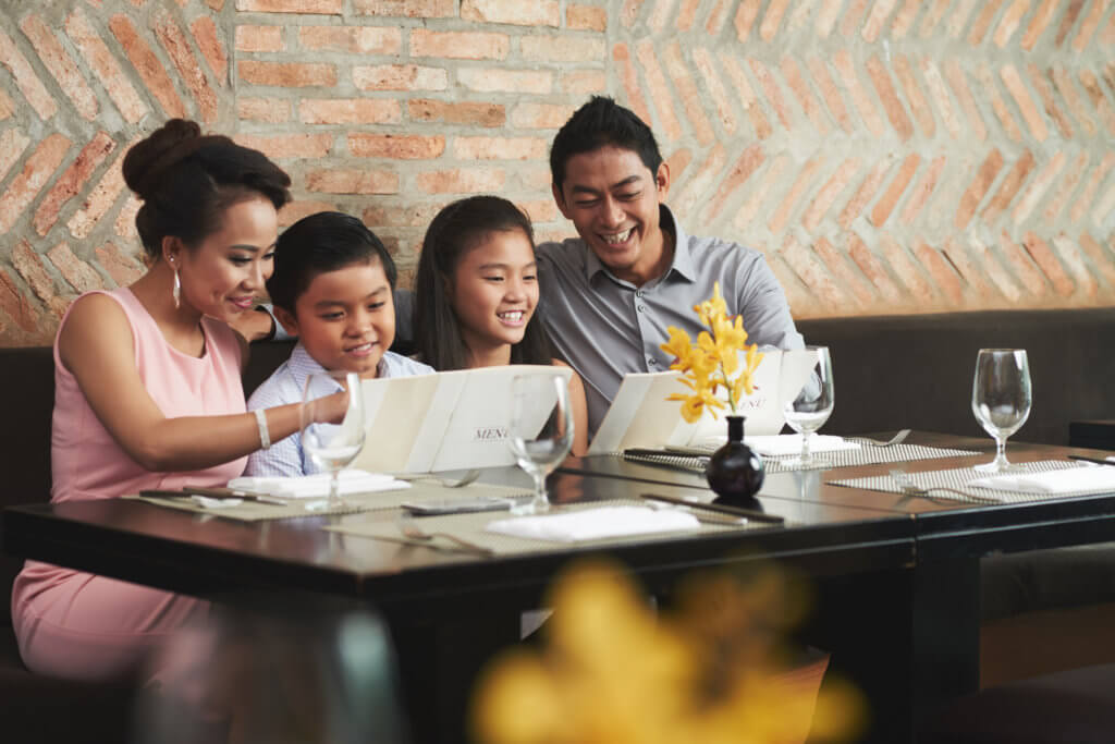 Smiling Vietnamese family reading menu at restaurant