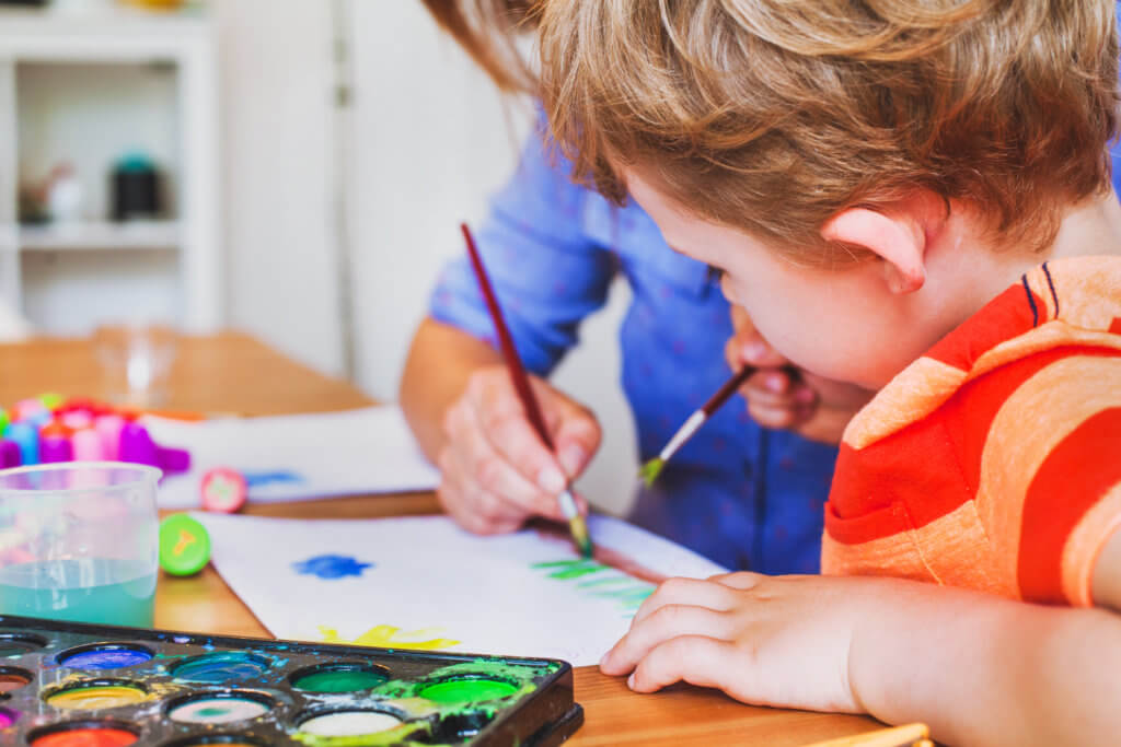 little child painting drawing with watercolors at home with his mom
