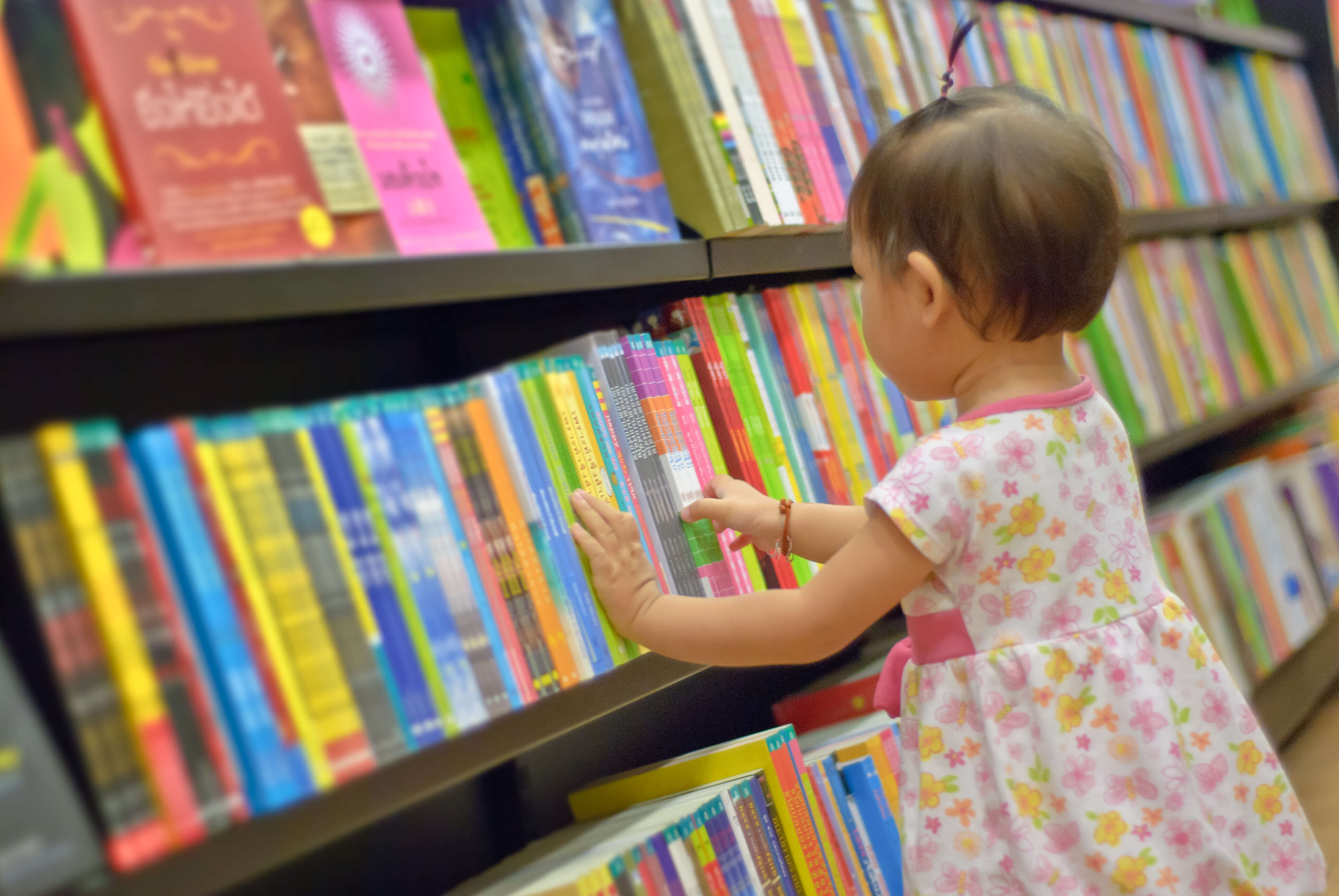 Asian Little girl is choosing a book in the library. A child is looking at the books in the library deciding which one to take home. Children creativity and imagination.