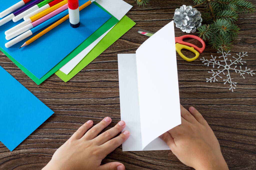 The child puts on paper the details of card Christmas. Made with your own hands. Children's art project crafts for kids. Craft for children.