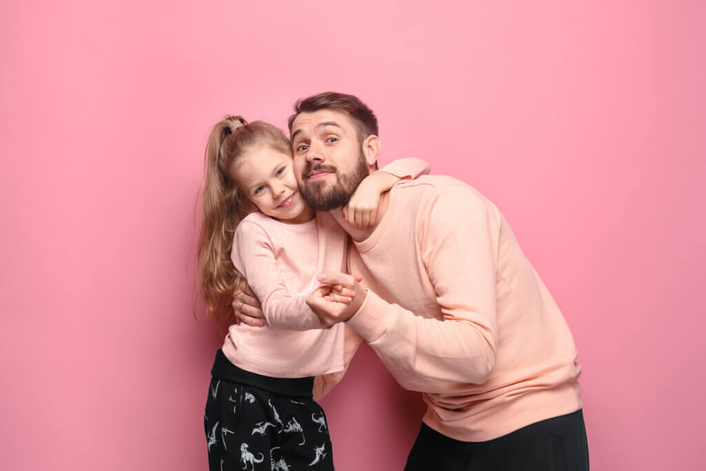 Young father with his baby daughter dancing at studio pink background
