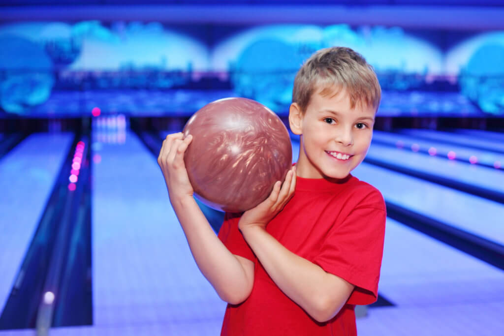 Little smiling boy dressed in red T-shirt holds ball in bowling club