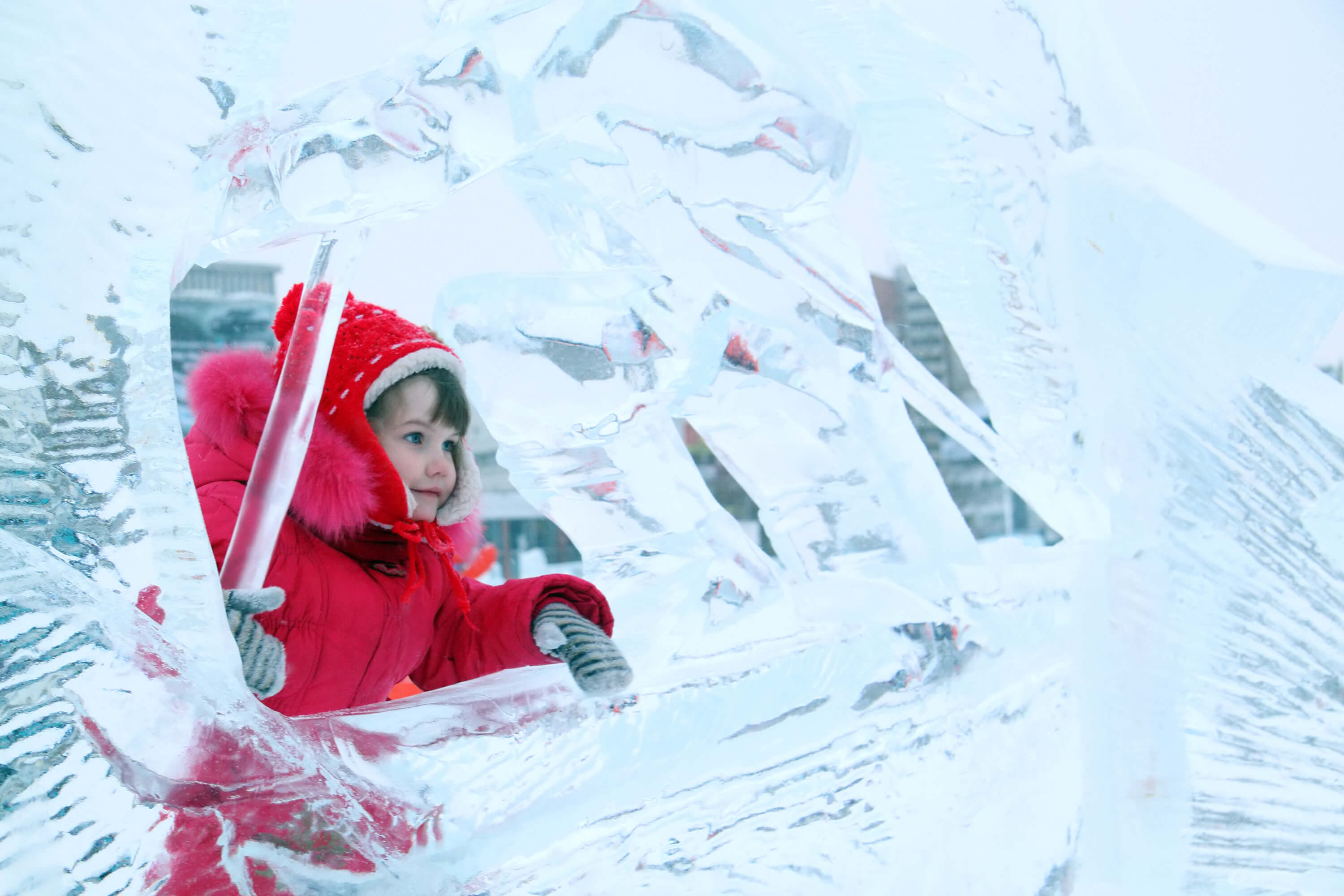Little happy girl in red warm clothes plays in ice sculpture at winter day