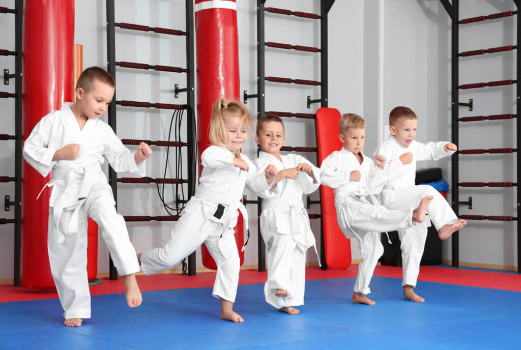 Little children practicing karate in dojo