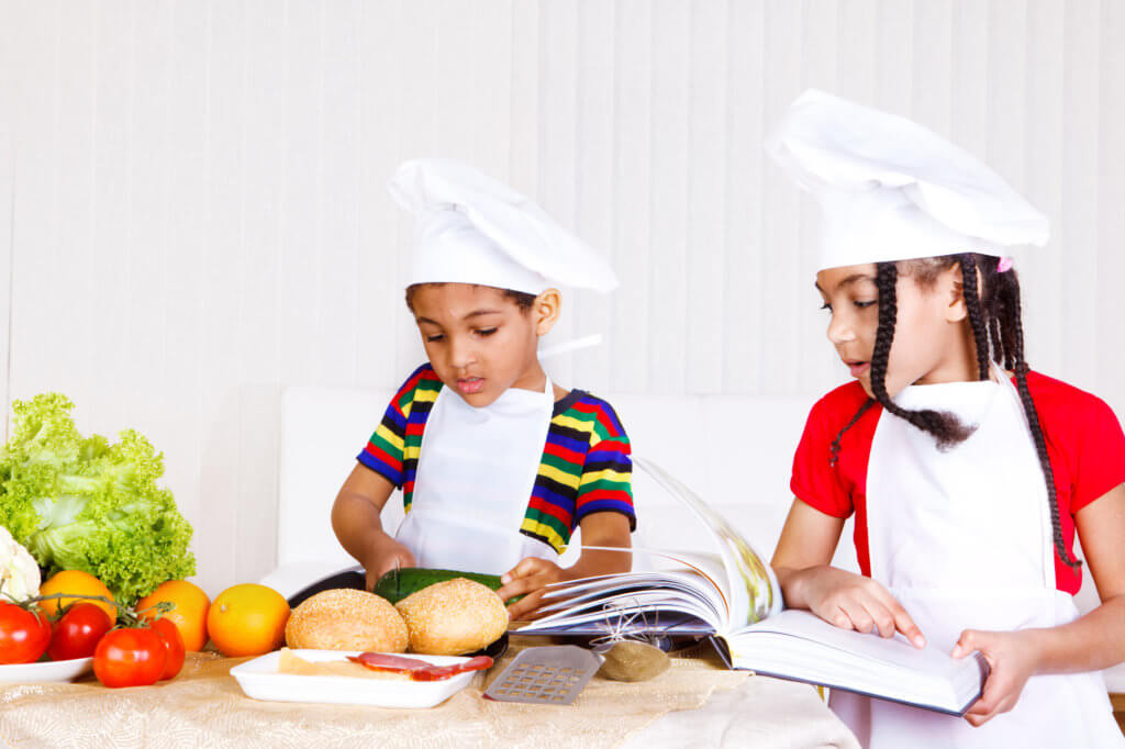 Two kids in white aprons and hats cooking