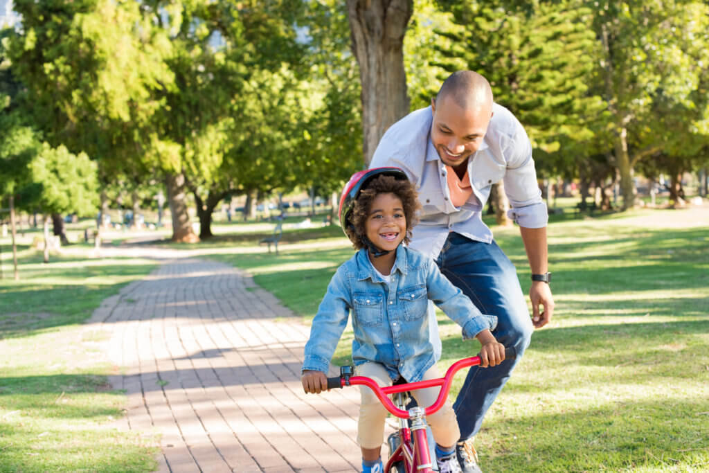 Lovely father teaching son riding bike at park. Happy father helping excited son to ride a bicycle in a summer day. Young smiling black boy wearing bike helmet while learning to ride cycle with his dad.