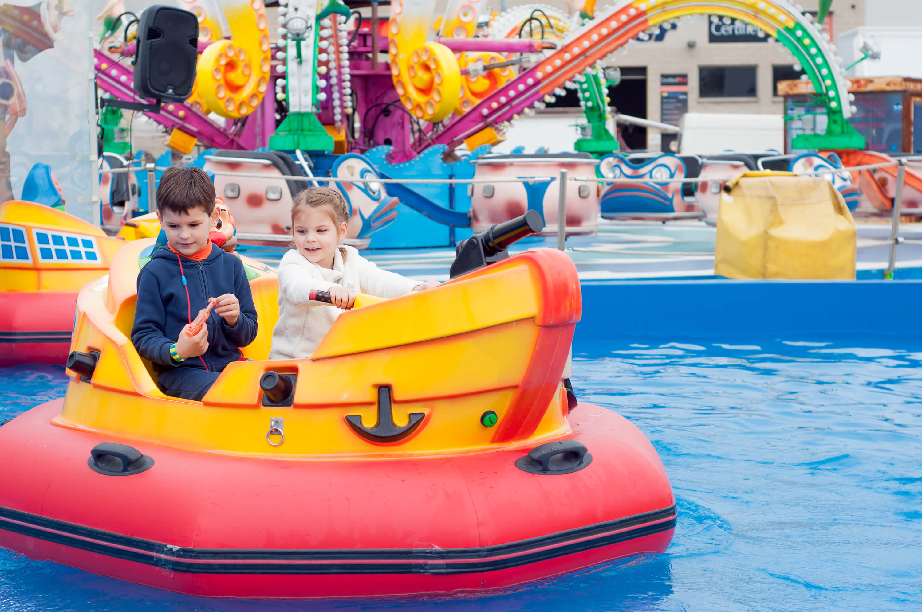 Beautiful Children Having Fun At An Amusement Park. Children On The Ship.
