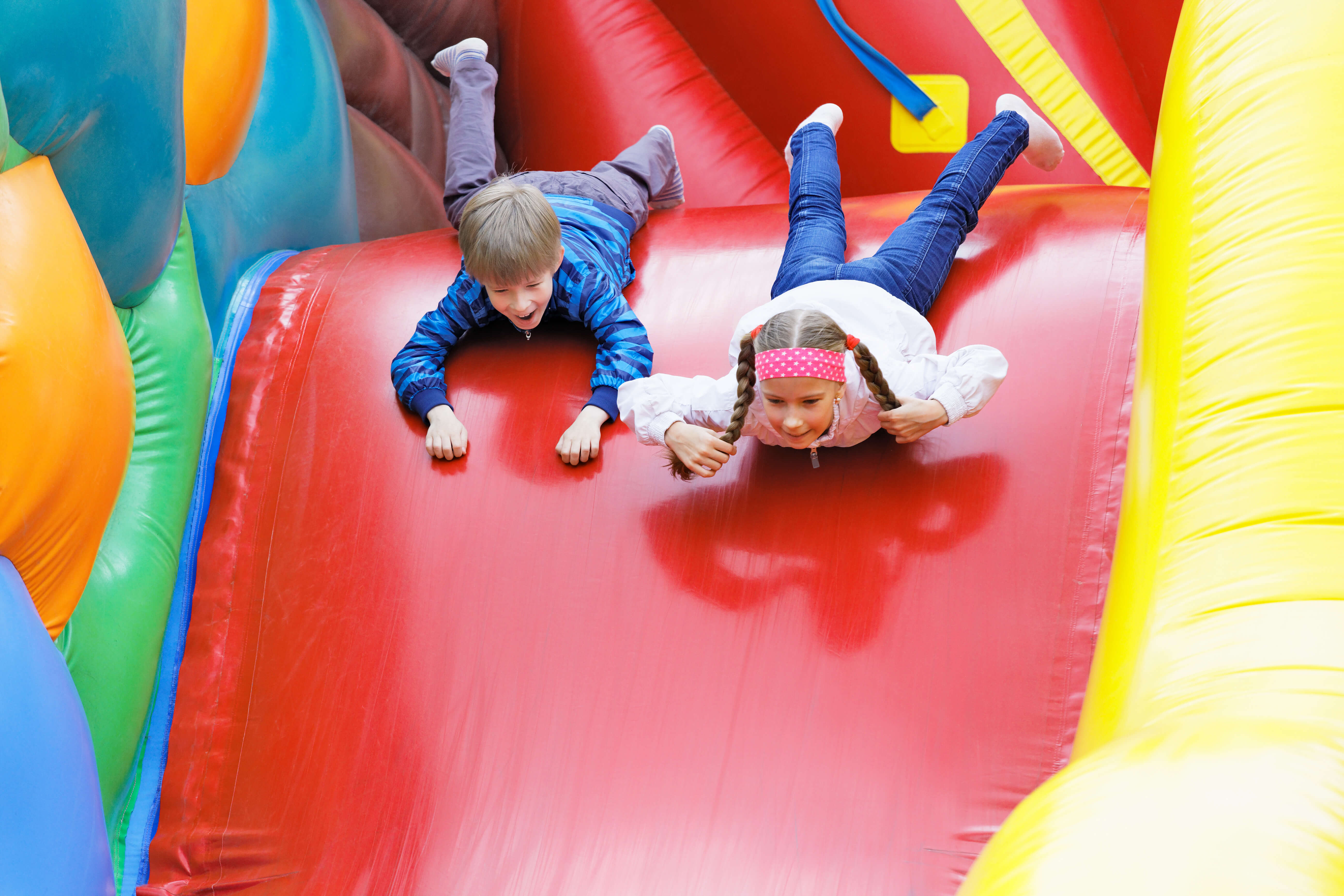 Brother And Sister Have Fun In The Park On An Inflatable Attraction