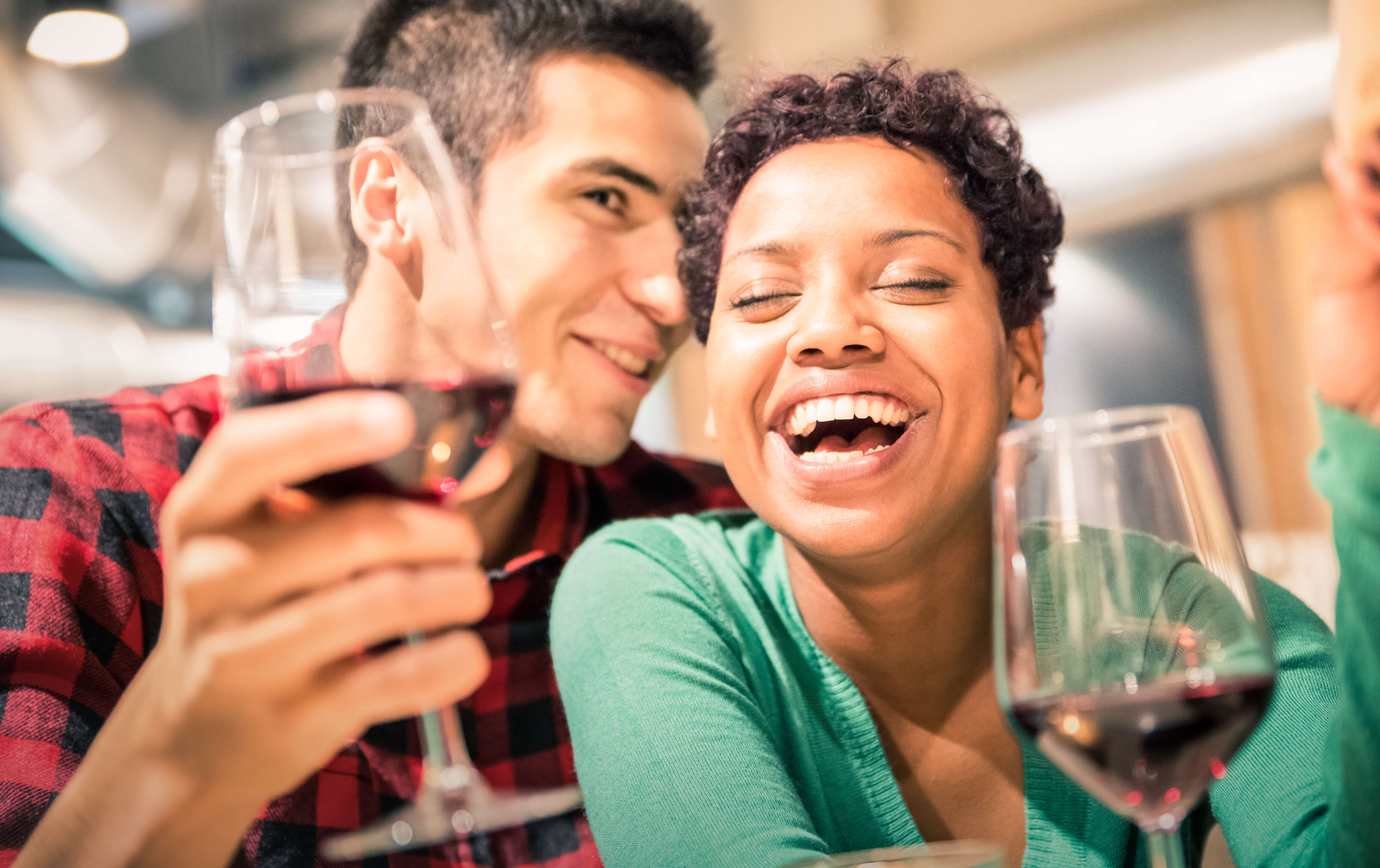 Happy Multiracial Couple Of Lover Drinking Red Wine At Fashion Restaurant - Handsome Man Whispers Soft Kisses In Beautiful Woman Ear - Relationship Concept With Boyfriend And Girlfriend On Warm Filter