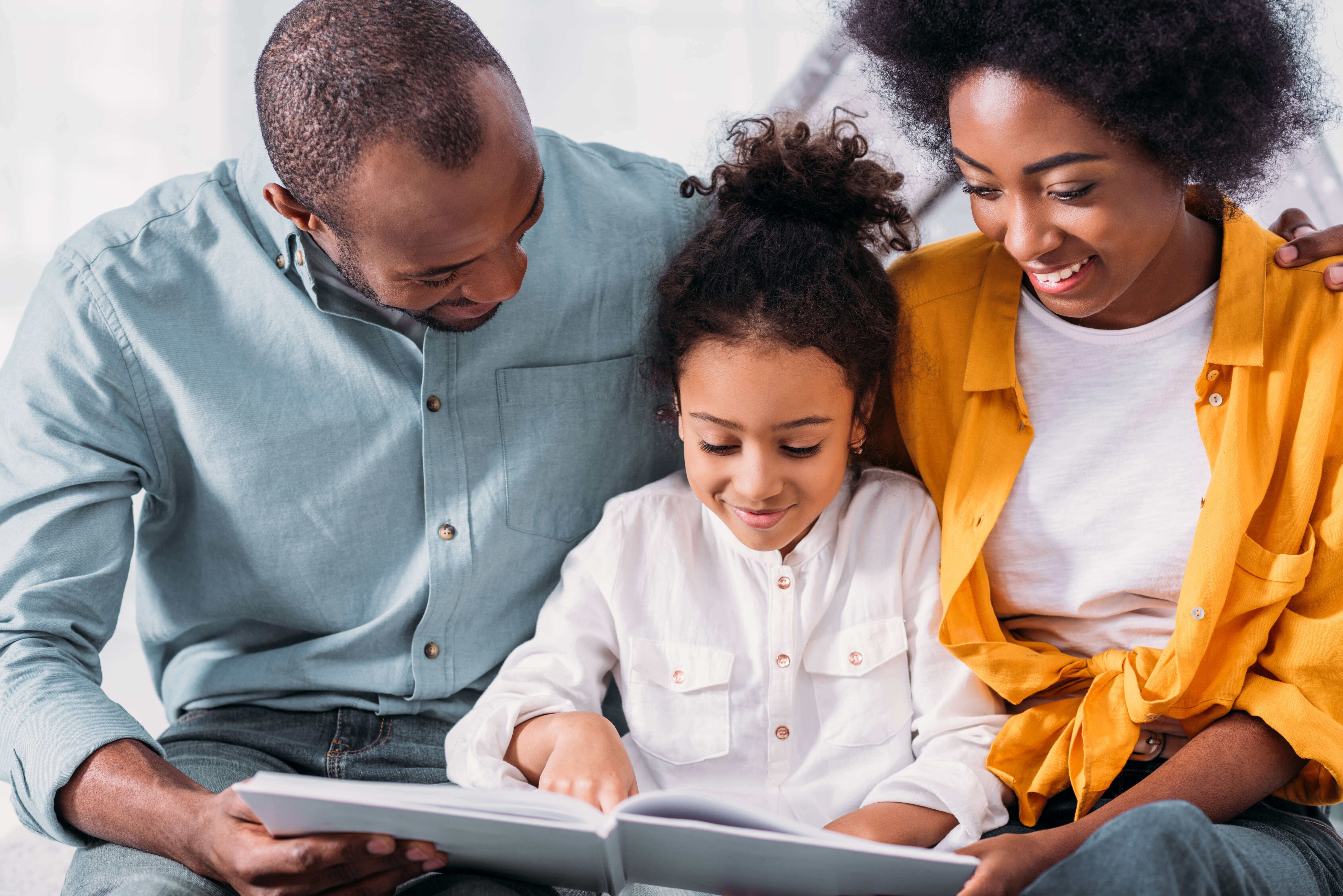 african american daughter reading for happy parents at home