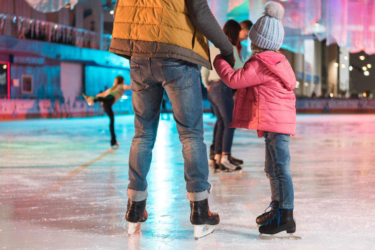 bb356277452 cropped shot of father and daughter holding hands while standing together  on skating rink