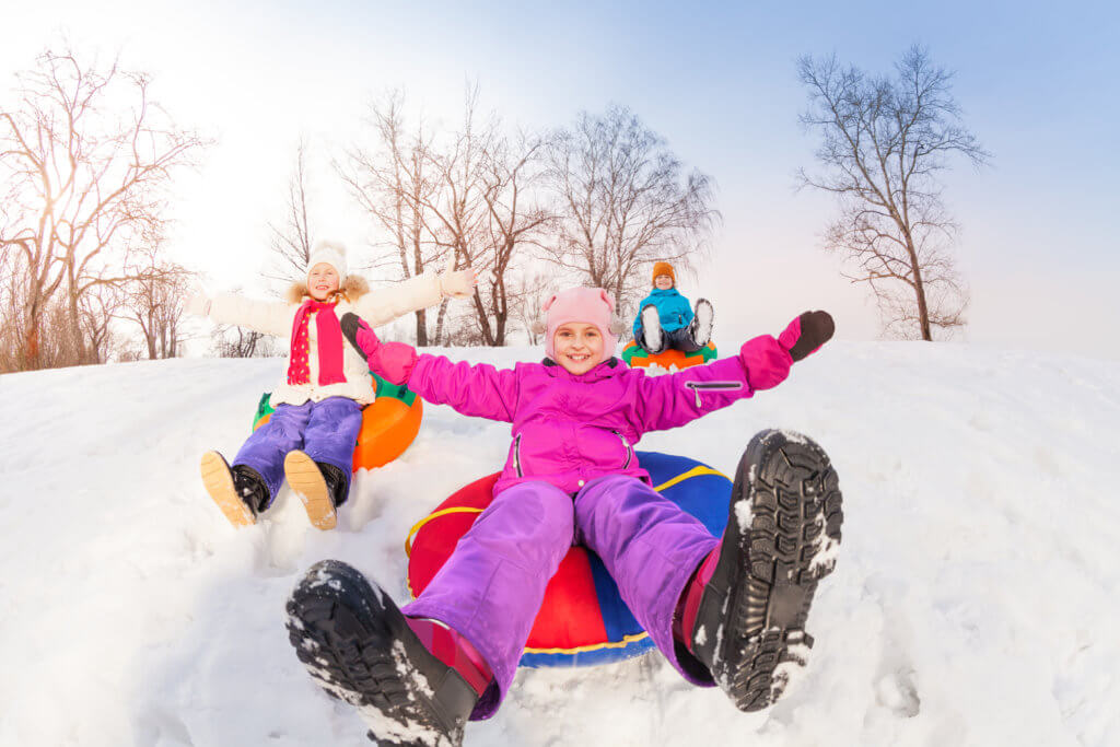 Girl and her friends sliding down the hill on the tubes with arms up during beautiful winter day with trees trunks on the background